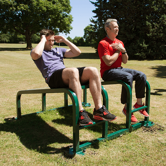 People doing sit ups at an outdoor gym station