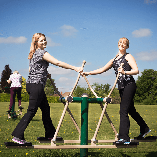 Two users exercising on the Double Cross Country Skier outside workout equipment