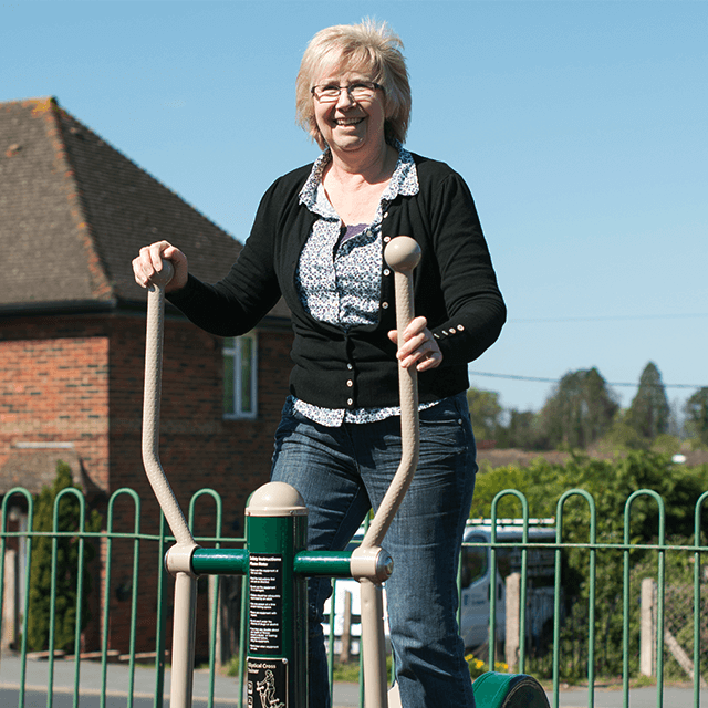 A woman using our outdoor cross trainer at a local park gym