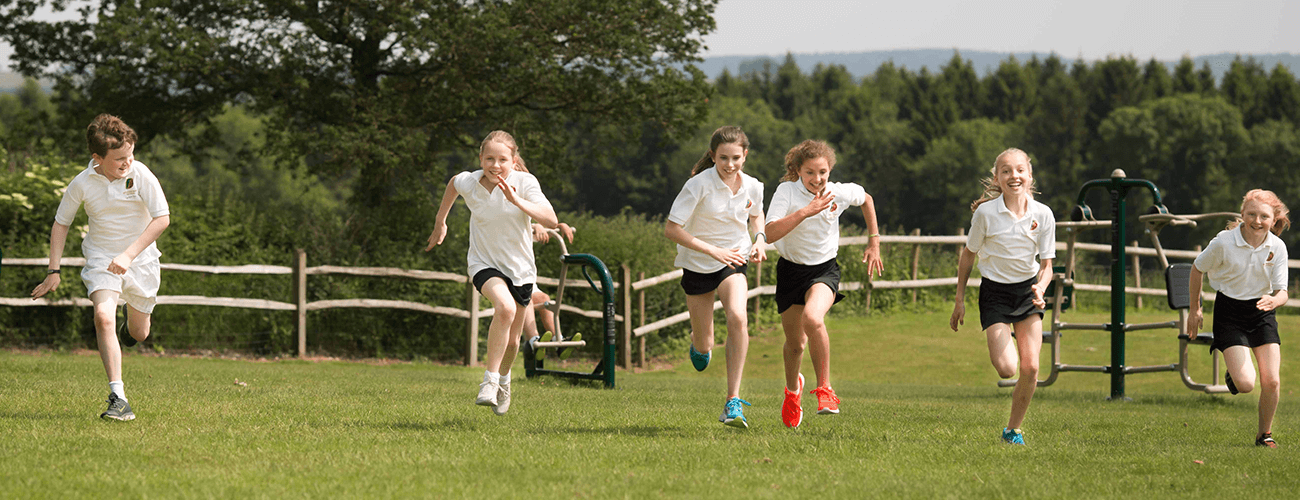 Secondary school children enjoying PE in their playing field